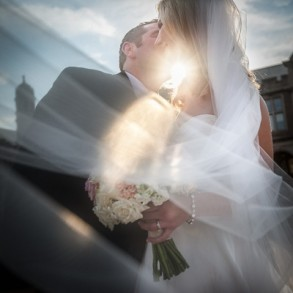 A groom give a kiss to the bride with the sun shining through their arms.